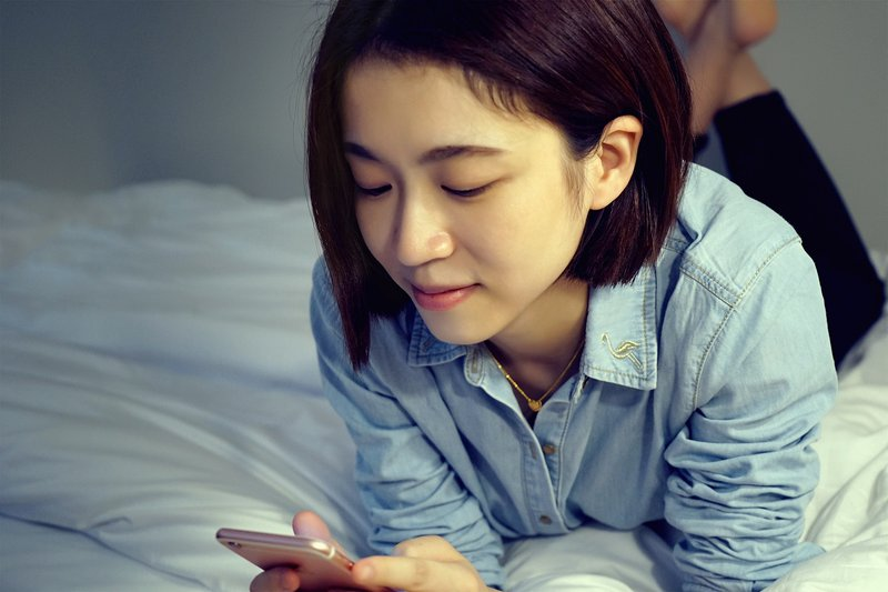 Chinese woman looking into her phone