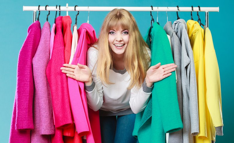 A woman coming out of a colorful wardrobe with amazement