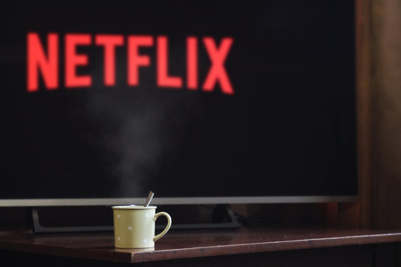 A cup kept in front of a screen; on it is written Netflix