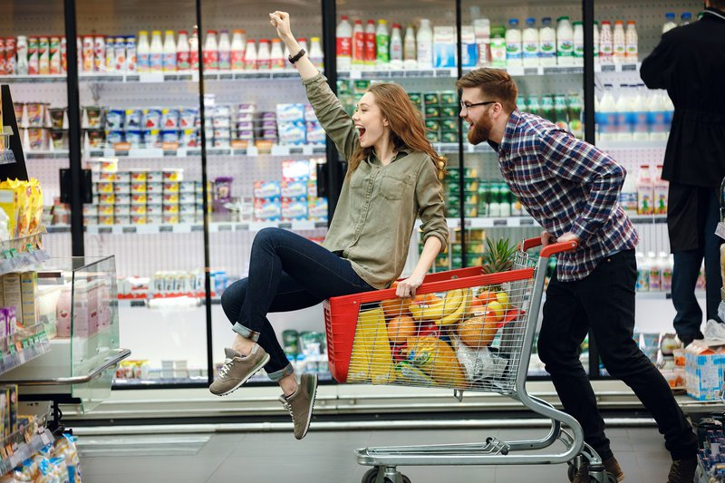 A woman riding on a shopping cart being pushed by a man
