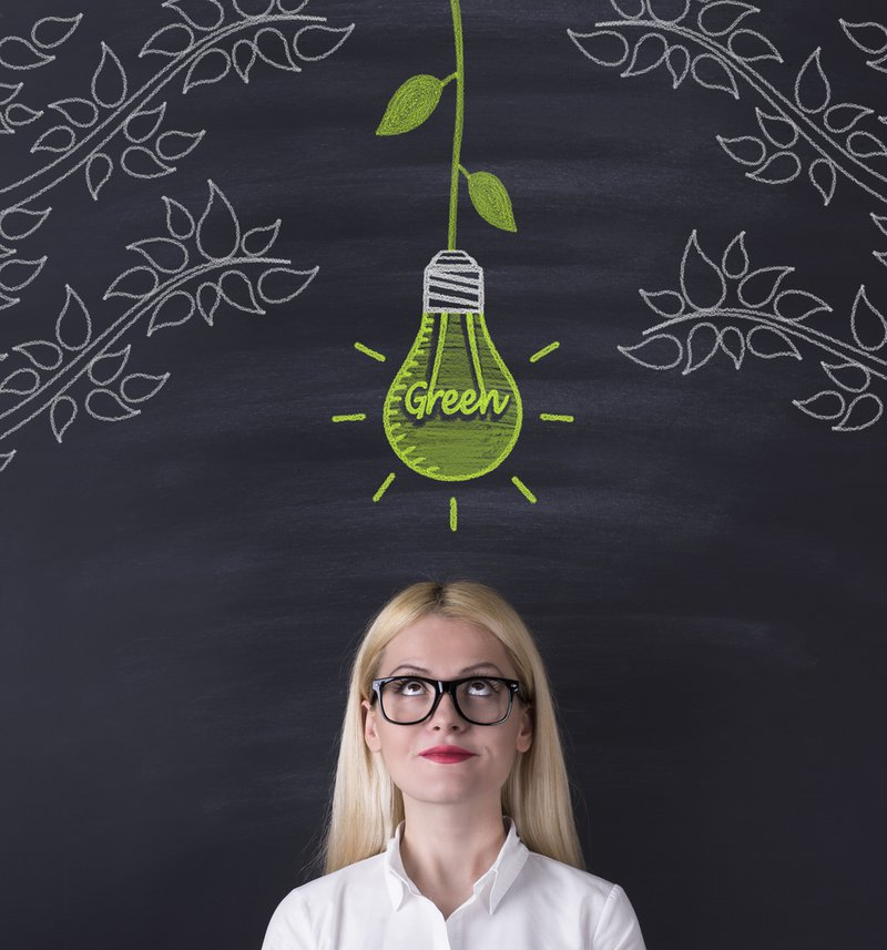 A woman looking at a green bulb placed right above her head
