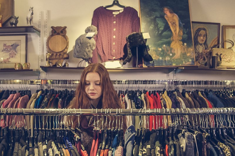 A young girl standing in a clothing shop