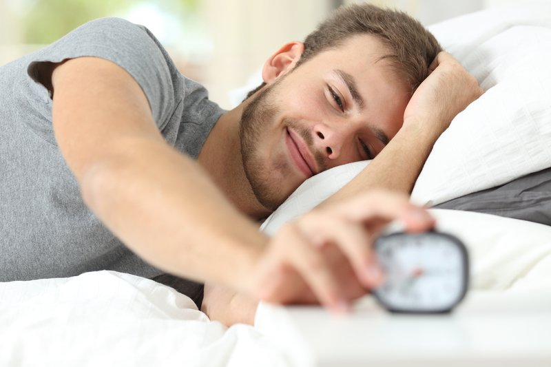 A man turning his alarm off