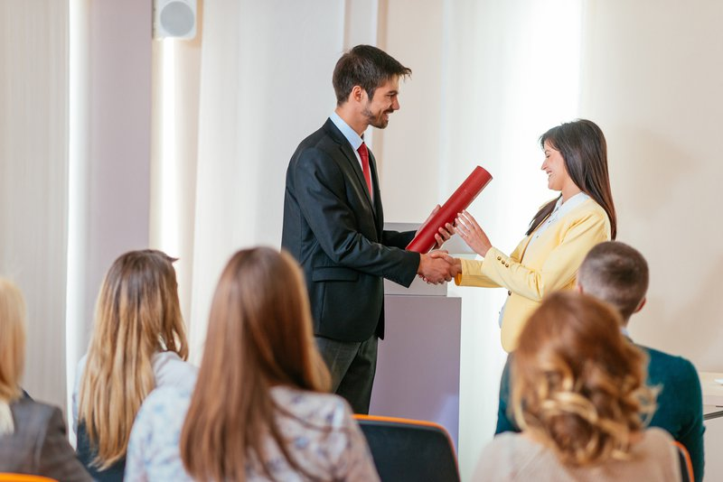 An employer handing over a file to his employee