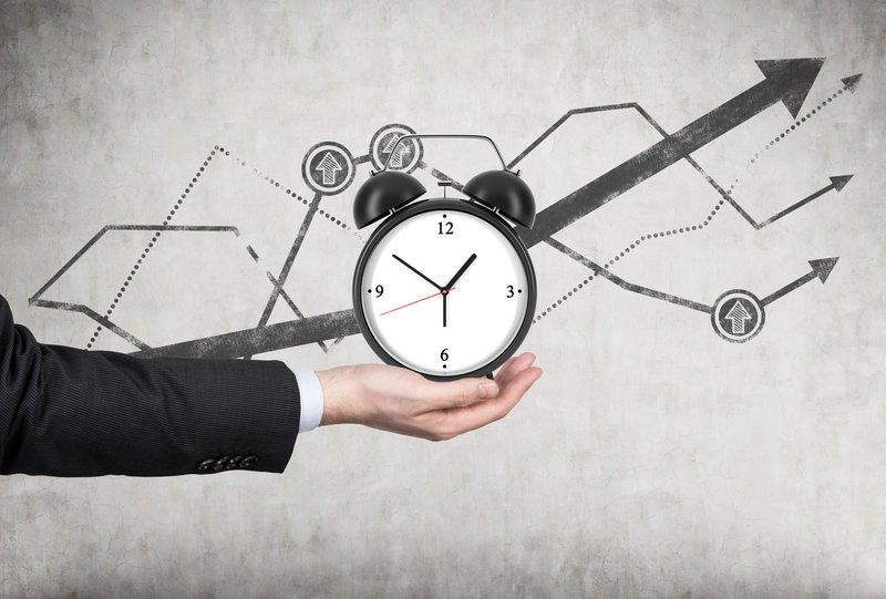 Businessman's hand holds an alarm clock