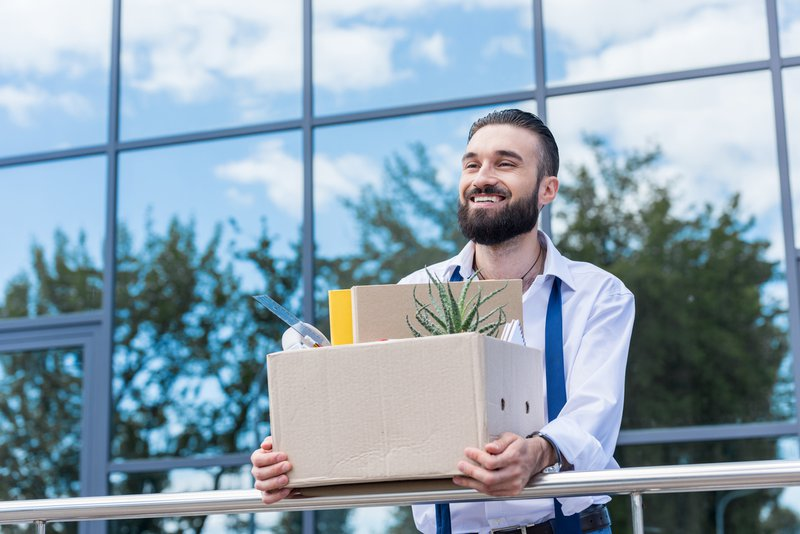 Happy businessman with cardboard box with office supplies in hands standing outside office building
