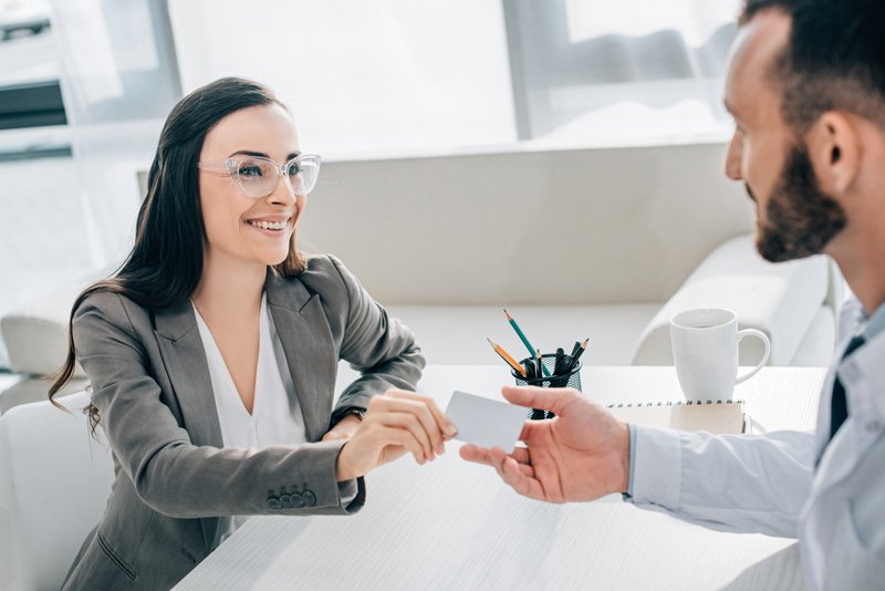 An interviewee giving business card to the interviewer at a job fair