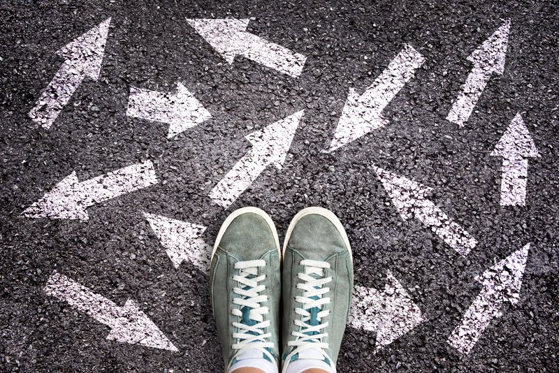 Sneaker shoes and arrows pointing in different directions on asphalt ground