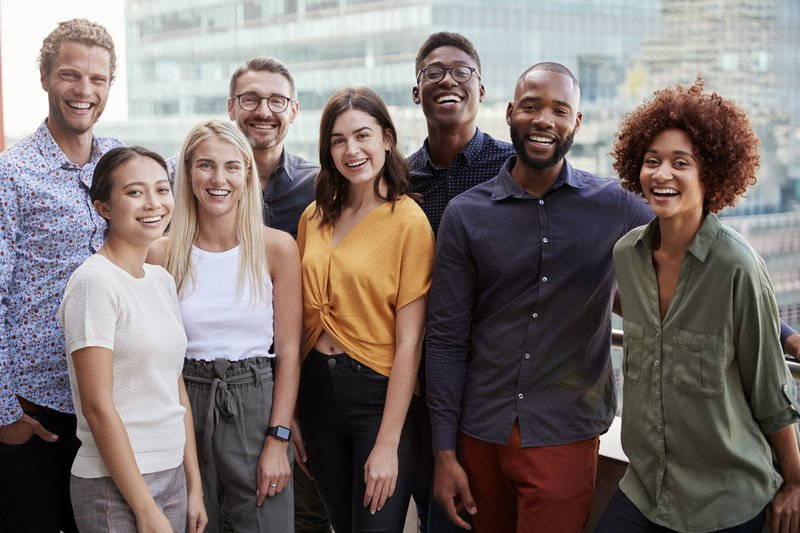 Group portrait of a diverse business team standing outdoors, three quarter length, close up