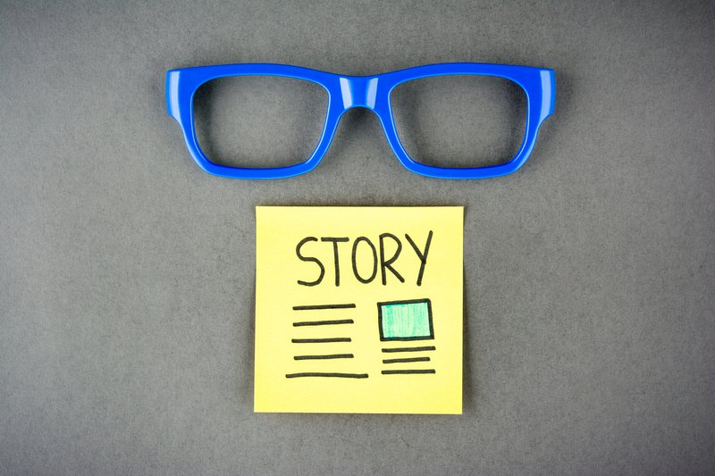 A blue spectacle with a yellow sticky note below it
