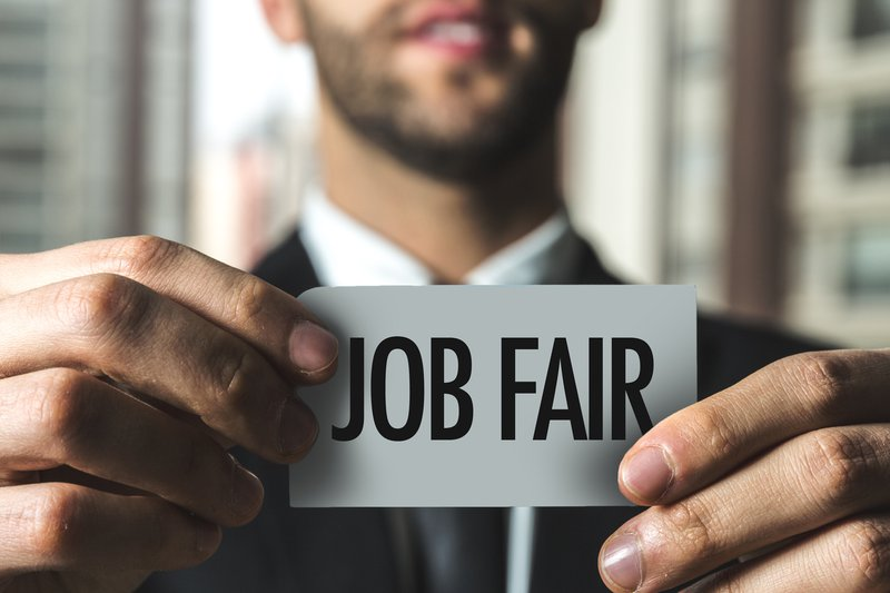 A professional holding a tag with Job Fair written on it