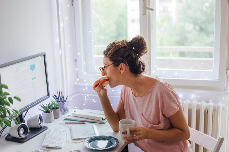A woman having her breakfast while working in her internship