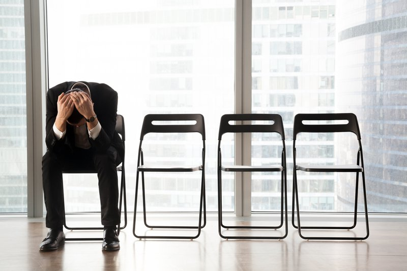 Stressed upset businessman sitting on chair, after job rejection