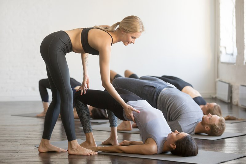 Group of young sporty people in Bridge pose learning yoga
