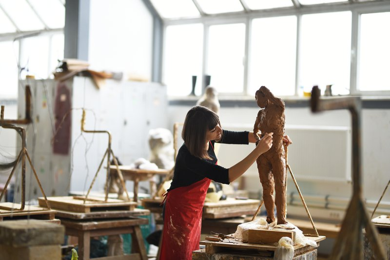 Young Female Sculptor is working in her