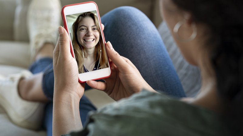 A young woman using smartphone for video call