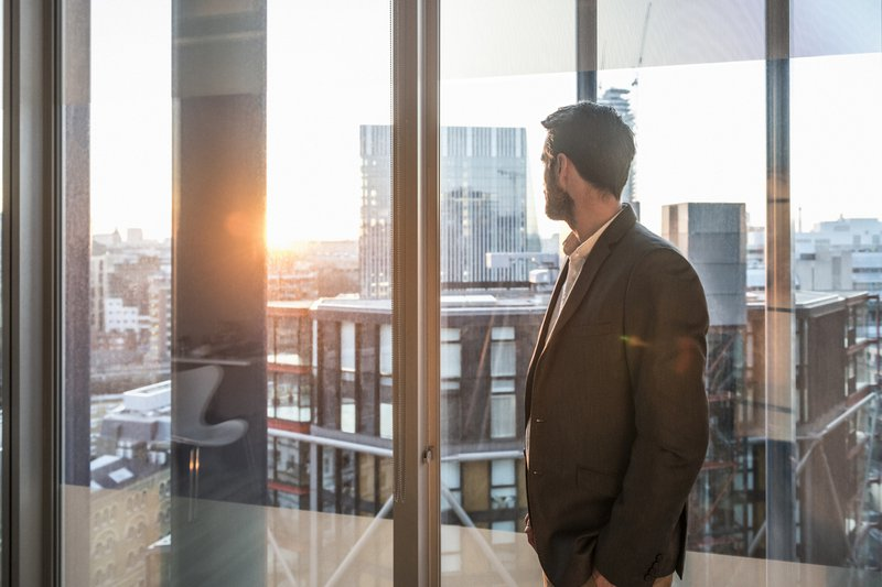 Businessman looking through office window in sunlight
