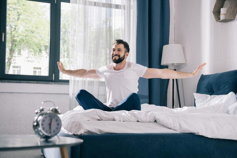 man in pyjamas in his bed happy