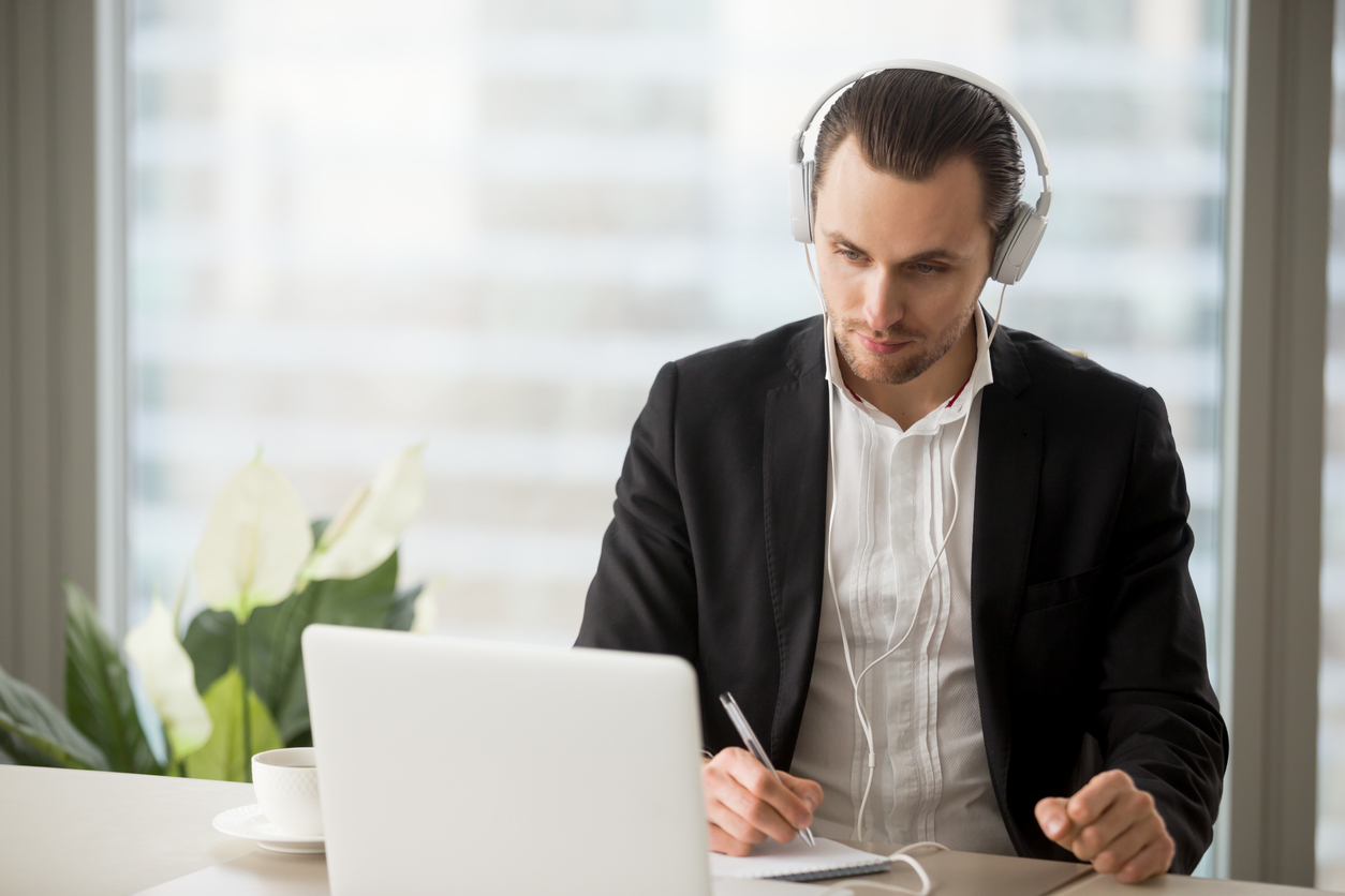 Businessman in headphones taking notes in front of laptop for a remote interview