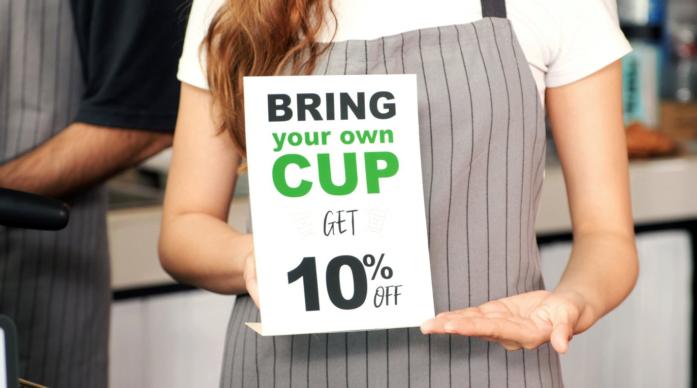 Bring your own cup get discount, Close up of waitress holding zero waste promotion poster
