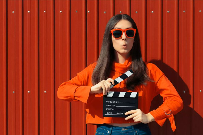 Beautiful Woman with Cinema Clapper on Red Background