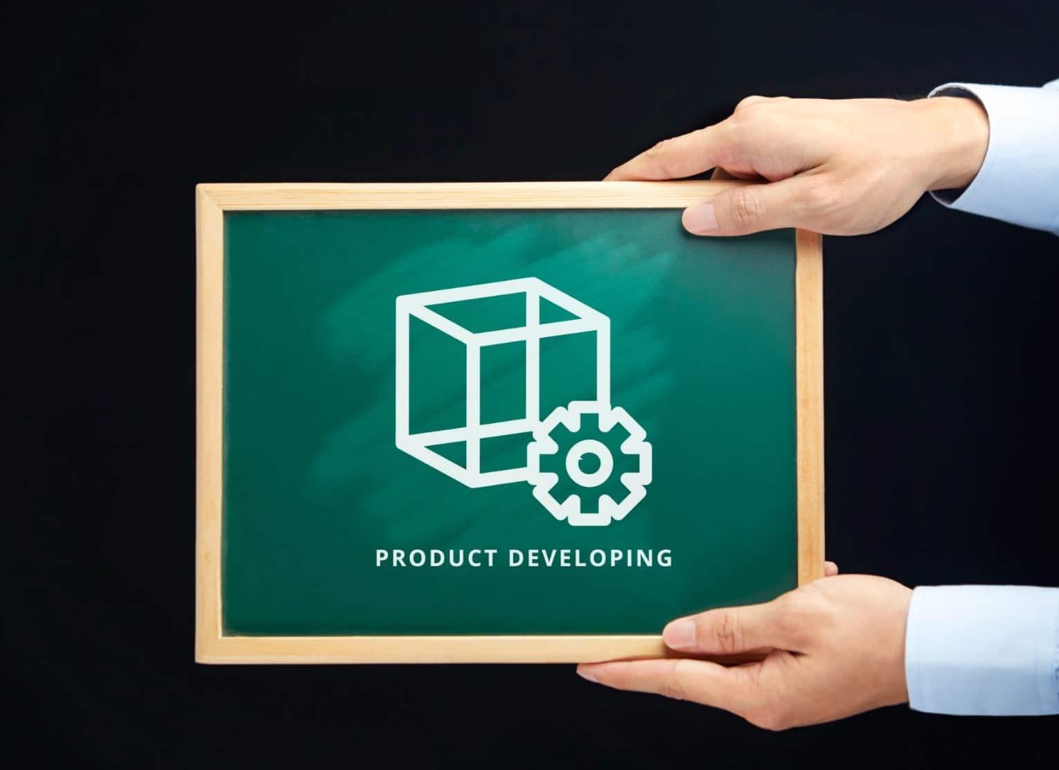 Man holding a blackboard written product development
