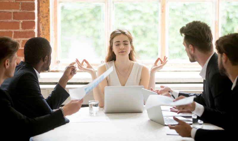 woman colleague doing yoga with other employees
