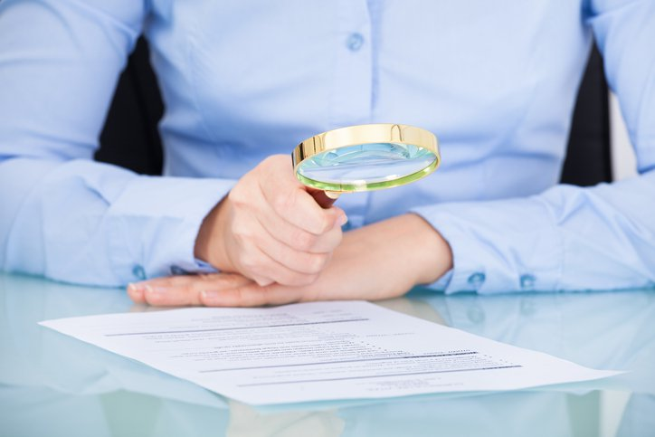 Businesswoman looking at resume with a magnifying glass