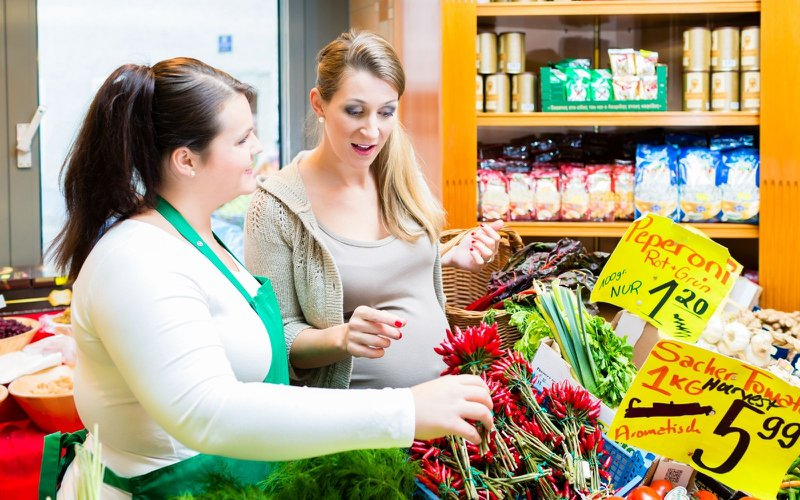 Two women buying groceries from a local mart
