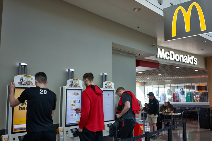 People standing near the self service kiosk of McDonald's