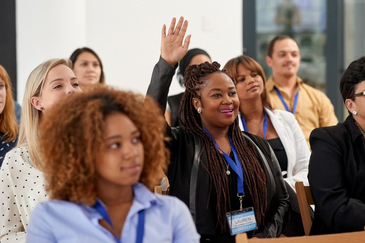 A professional raising her hand to ask question in a conference