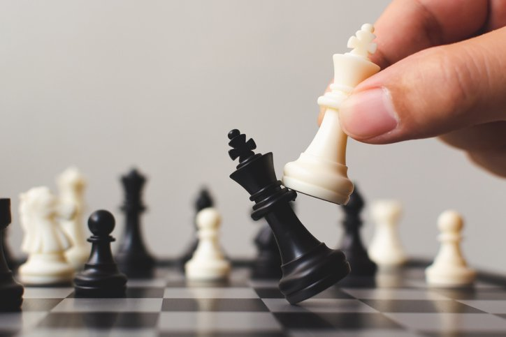 player on chess board game putting white pawn