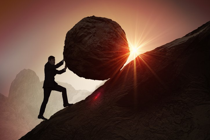 Silhouette of businessman pushing heavy stone boulder up on hill