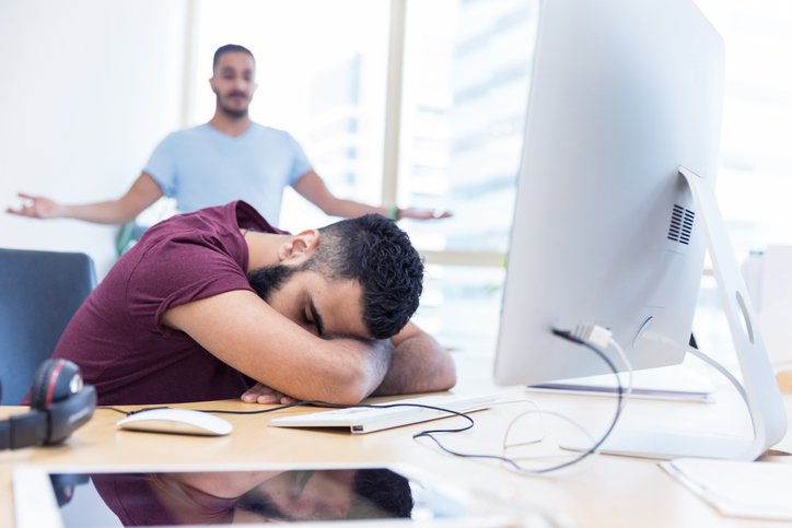An employee sleeping on his desk without a leader