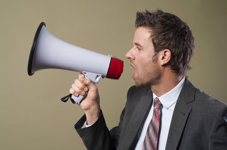 Business man shouting in megaphone to undifferentiated customers