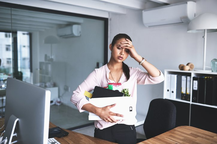 Business woman in stress with a box of her belongings in her hand