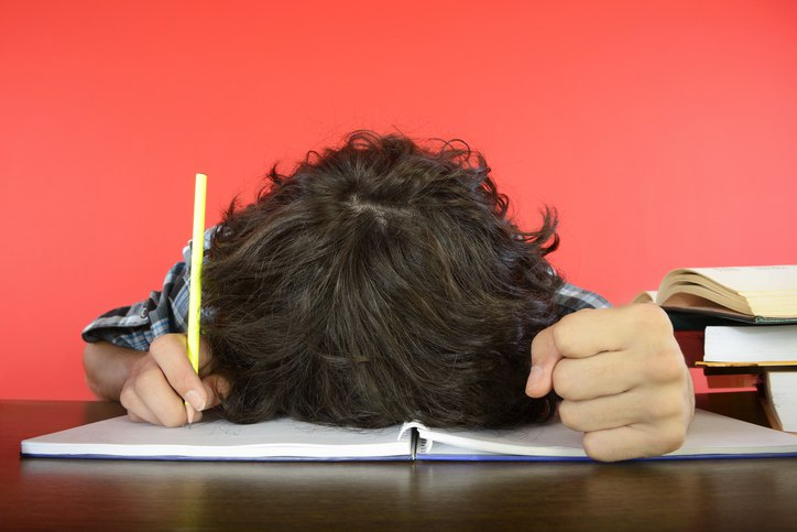 student with head on the notebook