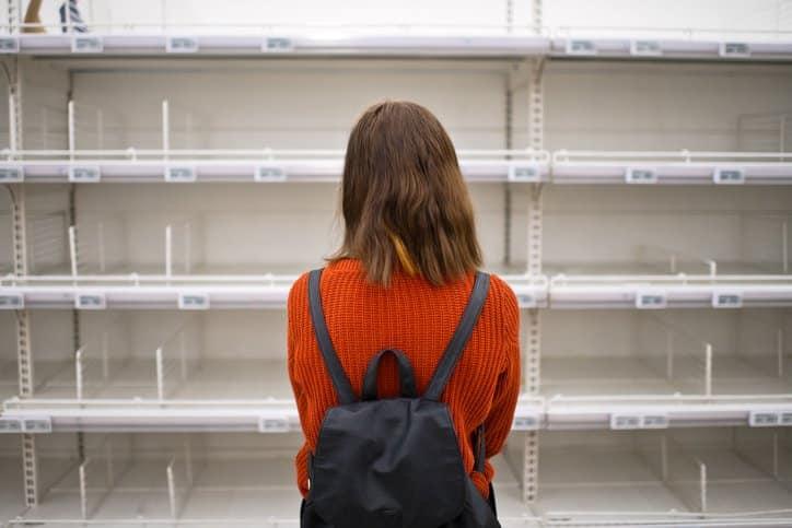 A customer looking at empty shelves at a supermarket