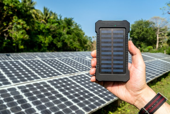 Poverbank in hand on the background of large solar