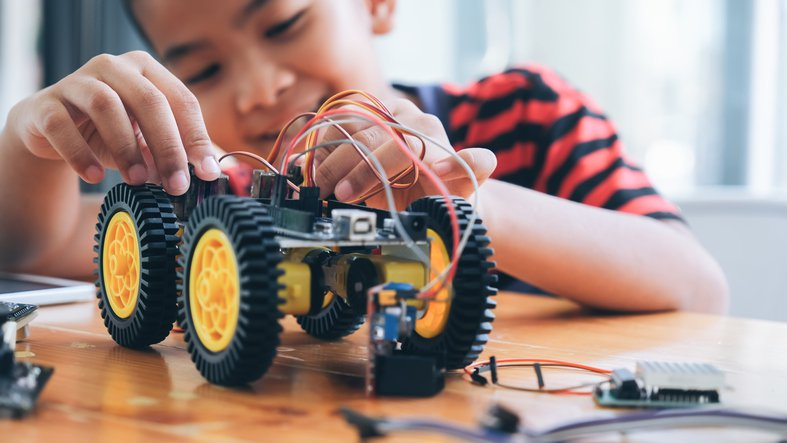 A young boy creating a robot at a lab.
